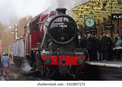 LOUGHBOROUGH, LEICESTERSHIRE, UK - JANUARY 24, 2014: LMS Stanier 8F 2-8-0 No. 48624 stands alongside Loughborough's Platform 2, which appears awash with enthusiasts during the GCR's 'Winter Steam Gala