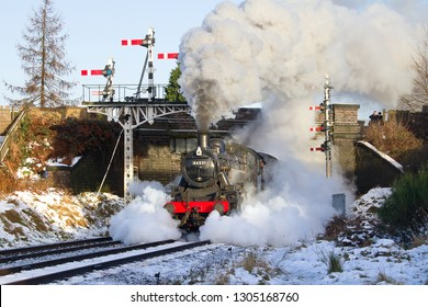 LOUGHBOROUGH, LEICESTERSHIRE, UK - JANUARY 26, 2013: Snow, cold air, and lots of steam make for an authentic Winter Gala at the GCR as LMS Ivatt Class 2 2-6-0 No. 46521 bursts from beneath the bridge.