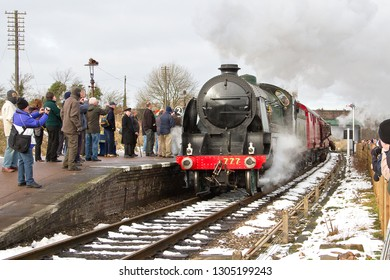 LOUGHBOROUGH, LEICESTERSHIRE, UK - JANUARY 26, 2013: With a loaded mailbag still swinging below the pickup net SR 'King Arthur' 4-6-0 No. 30777 'Sir Lamiel' speeds through Quorn and Woodhouse Station.