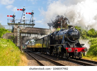 LOUGHBOROUGH, LEICESTERSHIRE, UK - JUNE 3, 2017: Steam locomotive LMS Stanier 8F 2-8-0 No. 48624 hauls a passenger train out of Loughborough during the Great Central Railway's  1940's Wartime Weekend.