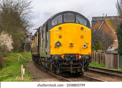 LOUGHBOROUGH, LEICESTERSHIRE, UK - MARCH 18, 2017: Diesel electric locomotive Class 37 No. 37714 'Cardiff Canton' heads out of Loughborough with a passenger train during the GCR's  Spring Diesel Gala.