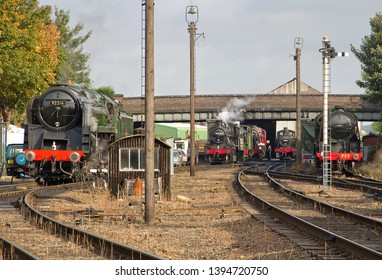 LOUGHBOROUGH, LEICESTERSHIRE, UK - OCTOBER 3, 2014: BR Standard 9F 2-10-0 No. 92214 stands at the head of 6 locomotives in Loughborough yard, all being prepared to work in the GCR's Autumn Steam Gala.