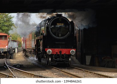 LOUGHBOROUGH, LEICESTERSHIRE, UK - OCTOBER 3, 2014: BR Standard 9F 2-10-0 No. 92214 passing under the Great Central Road Bridge makes for an atmospheric shot, as it departs Loughborough Station.
