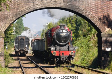 LOUGHBOROUGH, LEICESTERSHIRE, UK - OCTOBER 6, 2012: LMS Stanier 8F 2-8-0 No. 48624 has charge of the 9C13 minerals working, framed by a partially redundant bridge near Loughborough, on the GCR.