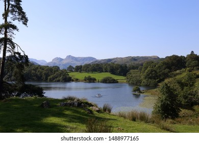 Loughrigg Tarn in the Lake District National Park in Northern England. People enjoying a paddleboard on the lake with views towards the Langdale Pikes.