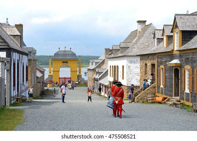 LOUISBOURG, NS, CANADA - JUL 30, 2016:  Actors in period costume walk down the main street of the Fortress of Louisbourg, which reenacts life at the French colony in the 1700s.