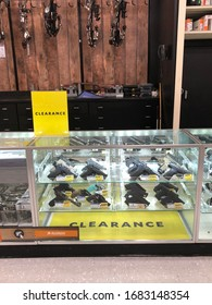 LOUISIANA, USA - MARCH 15, 2020: Different guns; shotgun, rifles, pistols, are displayed with clearance signs on a counter shelf in a store. Guns are for collectible, hunting, weapons, self defense.