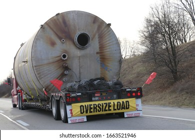Louisville Kentucky, February 15, 2020 Tractor Trailer transports large cylinder flagged as oversize load for highway commuters.