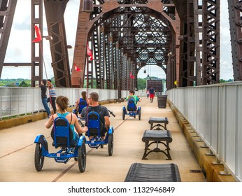 LOUISVILLE, KENTUCKY - JULY 3, 2018:  Tourists ride three wheeled cruiser trike bikes to tour Big Four Bridge in Louisville