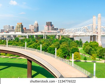 LOUISVILLE, KENTUCKY -  JULY 3, 2018:  Downtown Louisville skyline cityscape with Lewis and Clark Bridge, river front park land and shared walking bike path