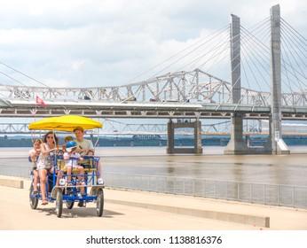LOUISVILLE, KENTUCKY - JULY 3, 2018:  Tourist family riding surrey bike to tour downtown urban waterfront path in Louisville, Kentucky
