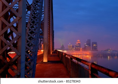 Louisville, Kentucky Skyline overlooking the Ohio River at sunrise during rush hour traffic.