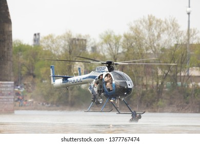 Louisville, Kentucky, USA - April 13, 2019: Thunder Over Louisville, Louisville Metro Police Department LMPD Air Operations MD 520N performing a recue demostration on the Ohio River
