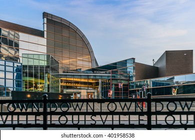 LOUISVILLE, KENTUCKY, USA - MARCH 23 2016: The Kentucky Center for the Performing Arts in Louisville Kentucky. The foreground is a black rod iron fence which says Downtown Louisville.