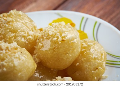 Loukoumades Greek pastry made of deep fried dough soaked in sugar syrup or honey and cinnamon.found in the Mediterranean, Middle East, and South Asia,
