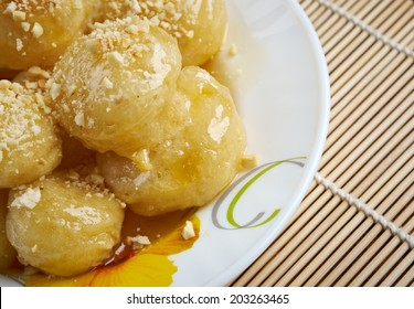 Loukoumades Greek pastry made of deep fried dough soaked in sugar syrup or honey and cinnamon.found in the Mediterranean, Middle East, and South Asia, from the Italian