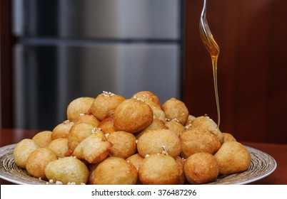 Loukoumades  are pastries made of deep fried dough soaked in syrup, chocolate sauce, or honey, with cinnamon and sometimes sprinkled with sesame