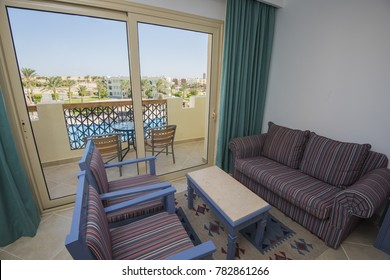 Lounge area in luxury hotel resort room with patio door and balcony view