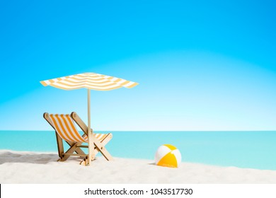 Lounge chair with parasol and beach ball on the coast, sky with copy space