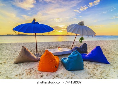 Lounge Chair in sunset in white sand which is a very attractive tourist destination in bintan