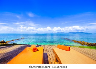 Lounge chairs on wooden deck with blue sky background close to the ocean and over looking to Koh Phangan the famous island near by Koh Samui Thailand.Vacation villas,resort or hotel