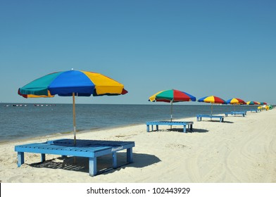 Lounge chairs, umbrellas, and oversized trikes scattered along Biloxi Beach in Mississippi on a spring day.