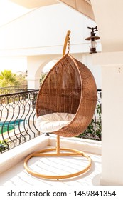 Lounge hanging chair in a balcony on a sunny day.