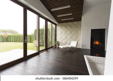 Lounge room with fireplace, chair, wood floor and garden view