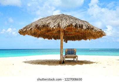 Lounger under cabana, parasol. Blue sea water and dramatic clouds. Oranjestad, Aruba. Famous Eagle Beach