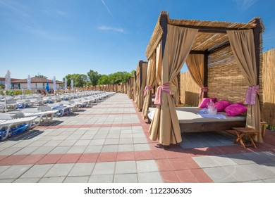Loungers with baldachin on hotel resort swimming pool