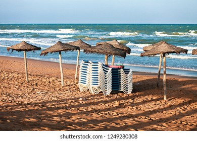 Loungers are stacked under parasols on the sandy beach to be stored during the night. Ocean in the background. Late afternoon - early evening light as the sun is setting.