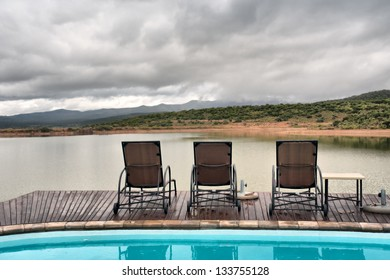 Lounges between swimming pool and lake in mountains. Shot in a game lodge near Oudtshoorn, Western Cape, South Africa.