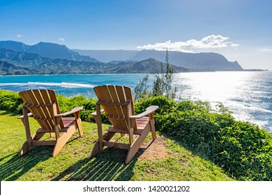 lounging chairs overlooking Hanalei Bay and the Na Pali coast Princeville Kauai Hawaii USA in the late afternoon sun