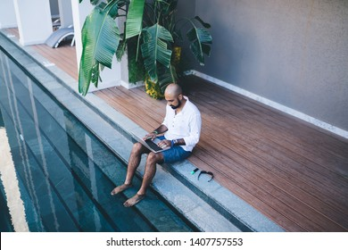 Lounging ethnic man sitting on edge of pool keeping feet in refreshing water while working and using laptop in leisure