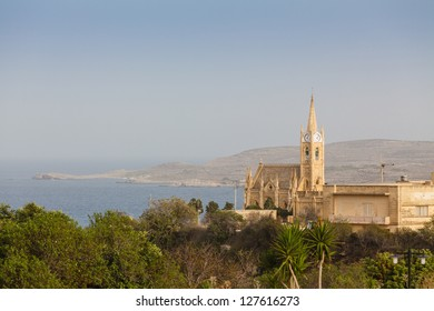 The Lourdes Chapel gothic church is dominating Ghajnsielem harbour, Gozo island, Malta