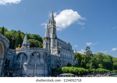 Lourdes, France, August 2013: The Basilica of Our Lady of Immaculate Conception of Lourdes  is built on the top of the rock above the Grotto