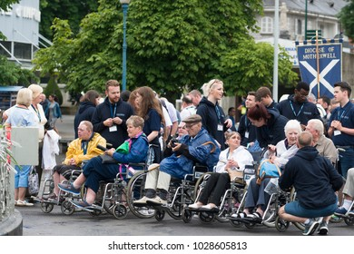 LOURDES, FRANCE - JULY 6, 2016: Volunteers and devotees in a wheelchair, in the Shrine of Our Lady of Lourdes.