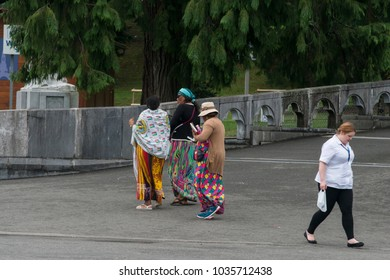 LOURDES, FRANCE - JULY 6, 2016: Pilgrims, with colorful African dresses, near the Shrine of the Virgin.