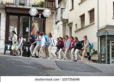 LOURDES, FRANCE - JULY 6, 2016: A group of teenage pilgrims, wearing a scout uniform, walk along the street accompanied by a nun.