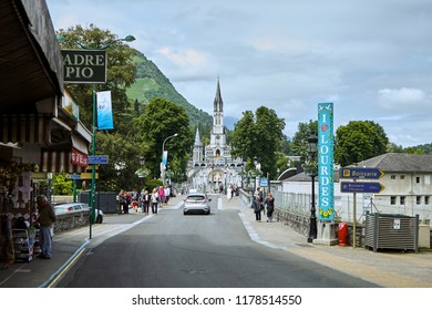 Lourdes, France - June 18, 2018: The road leading to the holy place. The Sanctuary of Our Lady of Lourdes or the Domain.