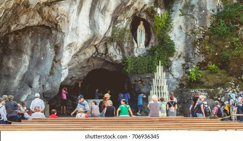 LOURDES, FRANCE - June 22, 2017 : Pilgrims enter the cave of Lourdes, France to light a candle and pray