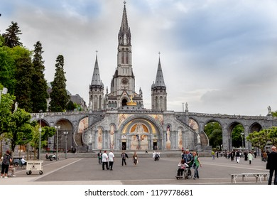 Lourdes, France - May 13, 2011: People returning from mass at The Sanctuary of Our Lady of Lourdes in France famous for the possible healing power of the water.