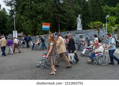 Lourdes, France - May 13, 2011: Pilgrims return from a religious service at the Sanctuary of Our Lady of Lourdes in Lourdes, France,