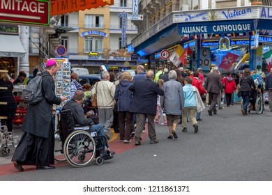 Lourdes, France - May 13, 2011: Pilgrims in the streets of Lourdes shop for religious articles. Candles are also acquired for religious services at Sanctuary of Our Lady of Lourdes.