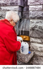 LOURDES - JUNE 15, 2019: View of a faithful man filling a bottle of holy water, Lourdes, France