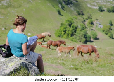 LOURDES,FRANCE - 05.17.2014: Girl reading a book in nature. Large and powerful horses on the hill above the city of Lourdes in the background. Photographed in early spring.