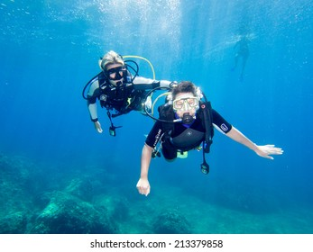 LOUTRA,GREECE-AUGUST 24 2014 :Female Scuba Diver taking part in a training dive with her Instructor.More women are taking up diving with dive schools around the world