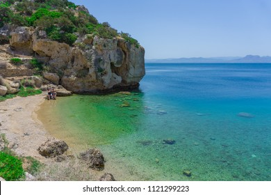 Loutraki, Greece/ June, 2018: Blue crystal waters at a small beach near archaeological site of Heraion, sanctuary of goddess Hera, in Perachora, Loutraki, Greece