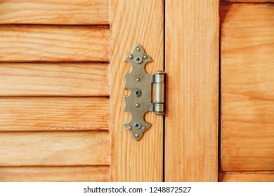 louvered wooden doors.iron hinge.brown yellow color.close-up view