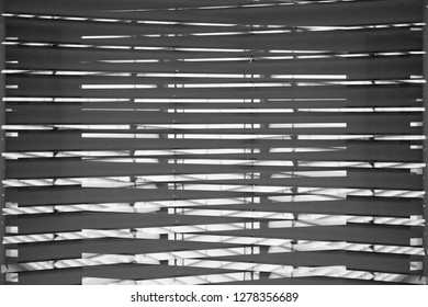Louvers / blinds / jalousie on windows. Grunge black and white close-up photo of interior fragment with reflections. Abstract background image on the subject of modern architecture.